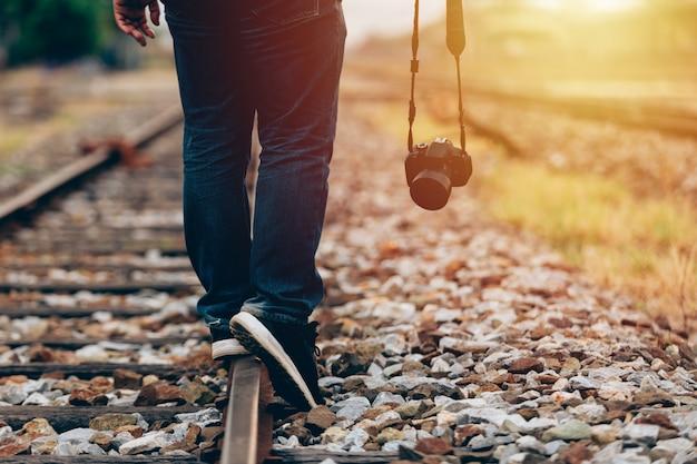 Gros plan d'un homme tenant une caméra numérique à pied dans le train