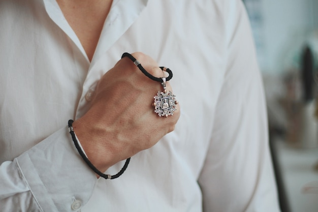 Gros plan d'un homme tenant un collier à breloques avec un pendentif en argent et un cordon noir