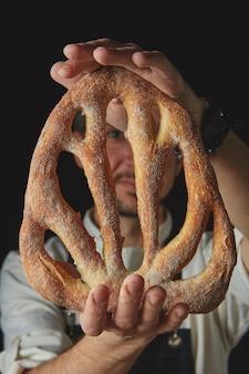 Gros plan d'un homme tenant du pain fougas frais