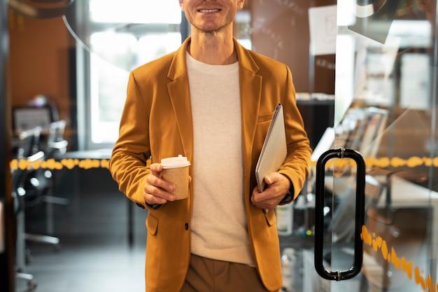 Gros plan homme tenant un ordinateur portable et une tasse de café