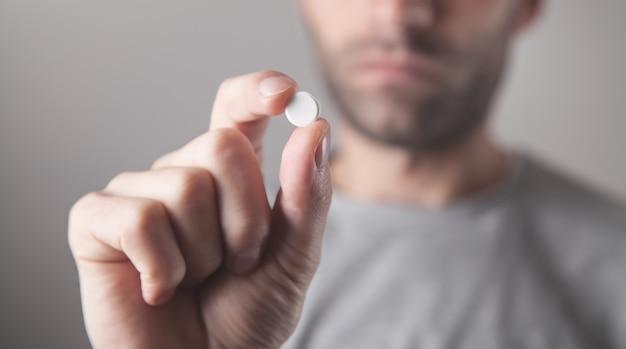 Gros plan d'un homme tenant une pilule.