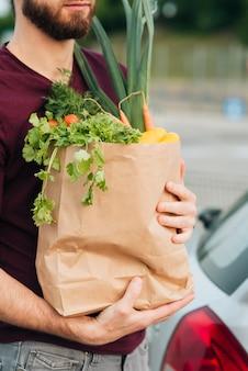 Gros plan homme tenant un sac d'épicerie