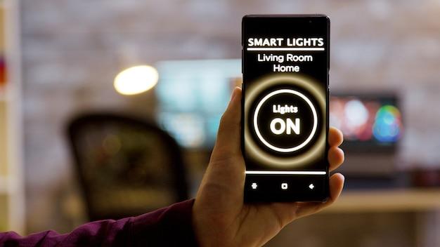 Gros plan d'un homme tenant un smartphone dans les mains avec une application d'éclairage intelligent dessus