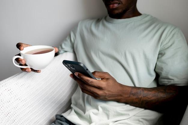 Gros plan homme tenant un téléphone et une tasse