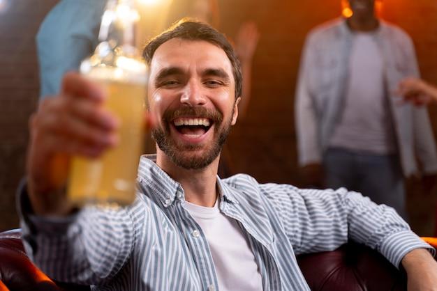 Gros plan homme tenant un verre au club