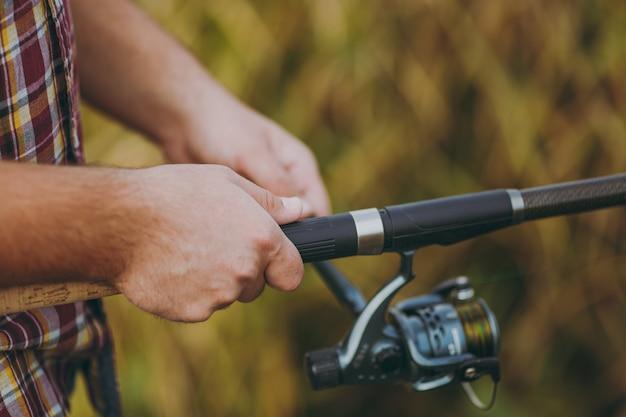 Gros plan un homme tient et détord un moulinet de pêche dans ses mains sur un fond marron flou. mode de vie, loisirs, concept de loisirs de pêcheur. copiez l'espace pour la publicité. avec place pour le texte.