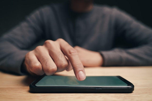 Gros plan d'un homme utilisant un smartphone sur la table en bois, recherche, navigation, médias sociaux, message, e-mail, marketing numérique internet, achats en ligne.
