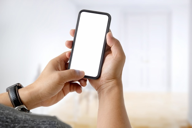 Gros plan d'un homme utilisant un téléphone intelligent à écran blanc mobile sur fond flou de bokeh.