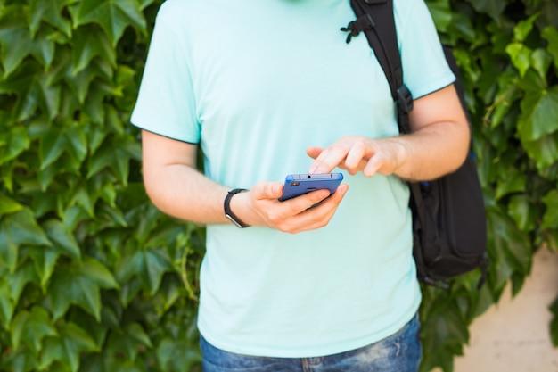 Gros plan d'un homme utilisant un téléphone intelligent mobile.