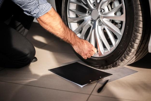Gros plan homme vérifiant les pneus de voiture