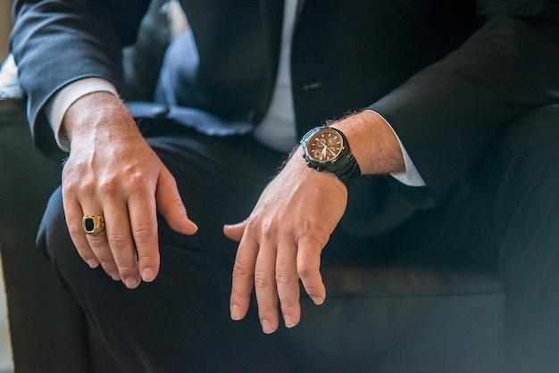 Gros plan d'un homme vêtu d'un costume, plus précisément: ses mains, sa bague et sa montre-bracelet