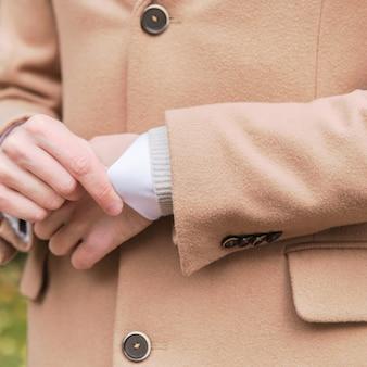 Gros plan d'un homme vêtu de plusieurs couches de vêtements - manteau en laine beige, pull en laine et col roulé blanc - sous-vêtements thermiques, extérieur.