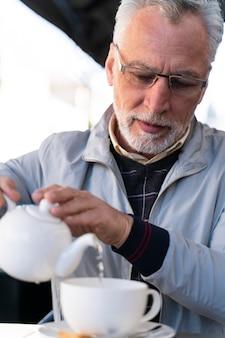 Gros plan homme vieux verser de l'eau