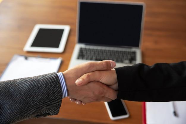 Gros plan d'hommes d'affaires se serrant la main dans la salle de conférence