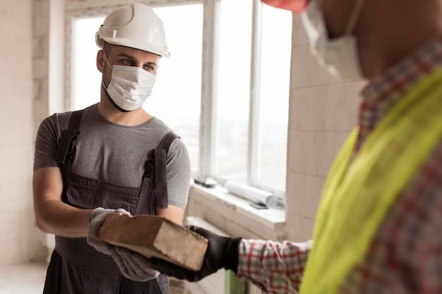 Gros plan des hommes de constructeur travaillant