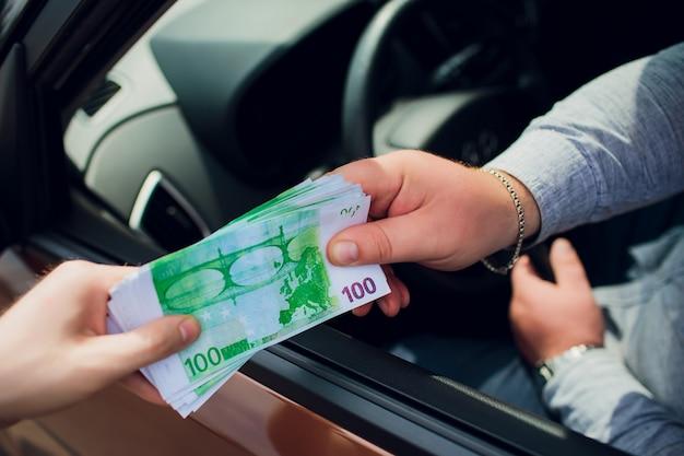 Gros plan, hommes, échange, euro chauffeur donnant de l'argent à un policier sur la voiture. concept de pot-de-vin.