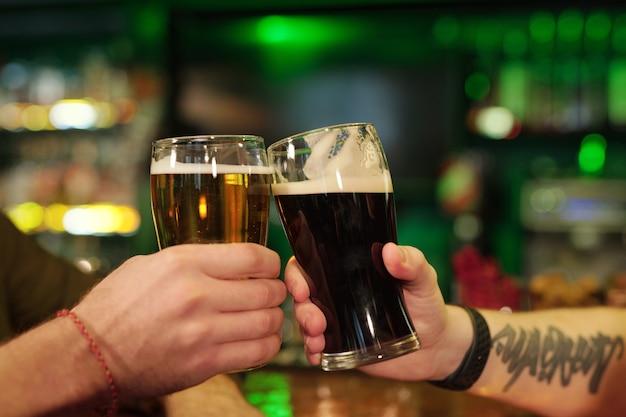 Gros plan d'hommes grillant avec des verres de bière tout en se reposant au bar