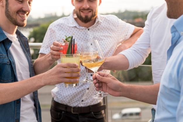 Gros plan des hommes portant un toast lors d'une fête