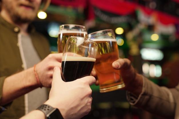 Gros plan sur des hommes tenant des verres de bière et portant un toast lors de leur réunion au bar