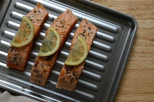 Gros plan horizontal de filets de saumon au citron dans une plaque de cuisson, sur une surface en bois de pin