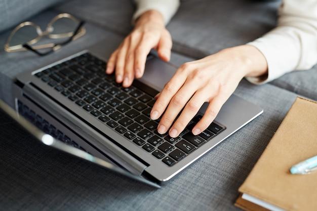 Gros plan horizontal grand angle de mains féminines en tapant quelque chose sur un ordinateur portable sur un canapé