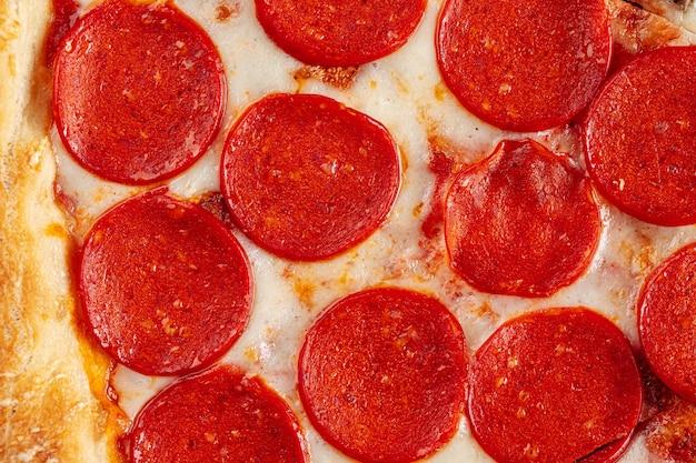 Gros plan horizontal sur la texture de la pizza au pepperoni et fromage