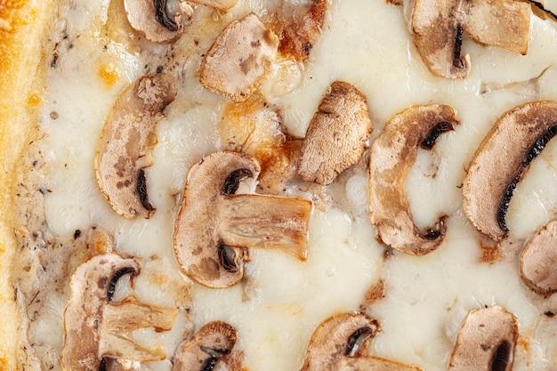 Gros plan horizontal sur la texture de la pizza aux champignons et au fromage