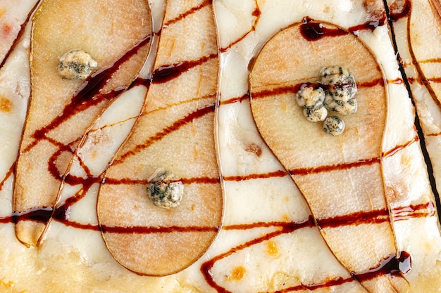Gros plan horizontal sur la texture de la pizza poire et fromage
