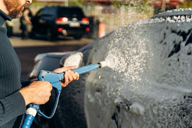 Gros plan horizontal d'une voiture noire avec de la mousse de nettoyage au service de lavage de voiture à l'extérieur avec un pulvérisateur à haute pression. concept extérieur de voiture propre