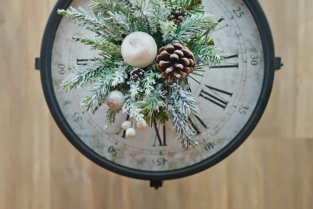 Gros plan sur l'horloge de noël avec des décorations du nouvel an. voir le haut de la branche d'arbre de noël avec cône et neige artificielle sur l'horloge. concept de noël et bonne année. espace de copie