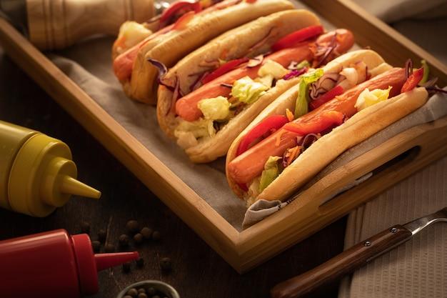 Gros plan, hot-dogs, à, moutarde, et, ketchup,, sur, bois rustique, et, sombre