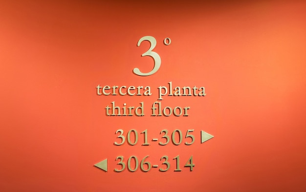 Gros plan de l'hôtel signe des directions dans un mur rouge