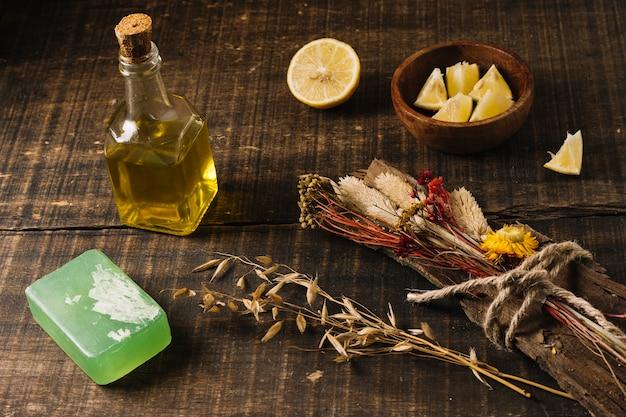 Gros plan huile d'olive avec barre de savon citron et plantes