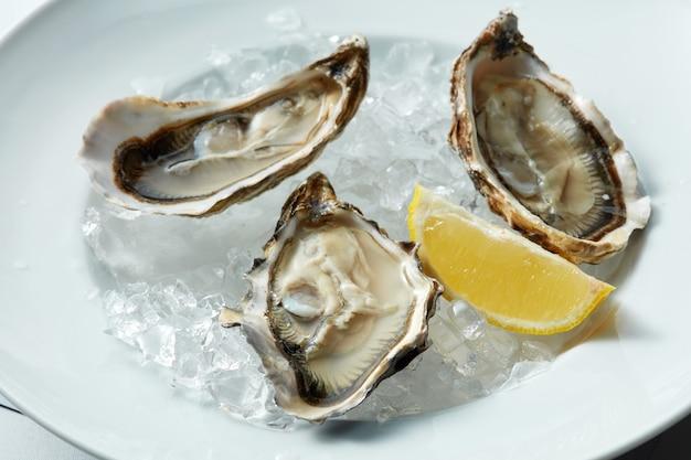 Gros plan d'huîtres crues servies sur la demi-coquille sur glace au citron.