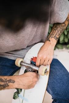Gros plan, de, humain, mains, ajustement, skateboards, roue