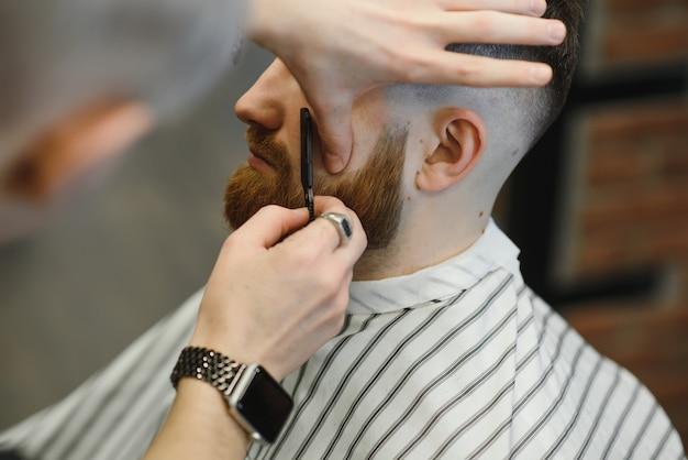 Gros plan image de barbier raser un homme avec un rasoir en acier tranchant.