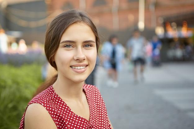 Gros plan image de charmante jeune femme magnifique avec une peau bronzée parfaite, des dents droites et des cheveux rassemblés en queue de cheval avec un beau sourire positif, posant à l'extérieur dans le parc