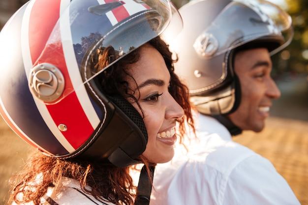 Gros plan image de couple africain heureux monte sur une moto moderne dans la rue