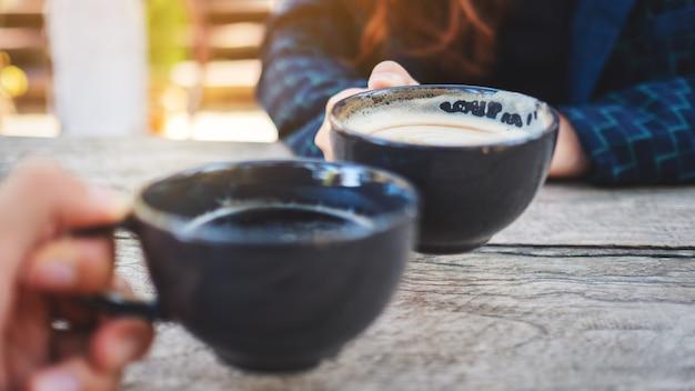 Gros plan image de deux personnes tinter des tasses à café sur une table en bois