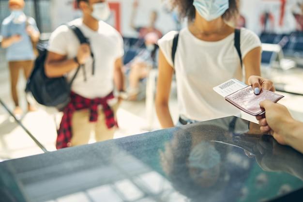 Gros plan image d'une femme donnant une carte d'embarquement avec un document pour le gardien d'embarquement pour le contrôle jusqu'au vol