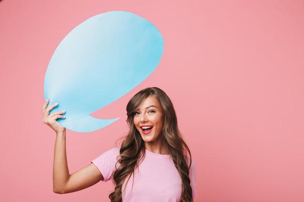 Gros plan de l'image d'une femme européenne joyeuse dans des vêtements décontractés tenant une bulle de pensée bleue vierge au-dessus de sa tête, fond pour votre texte, isolé sur fond rose