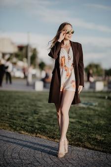 Gros plan image de femme heureuse dans des vêtements de lunettes de soleil posant sur le côté à l'extérieur