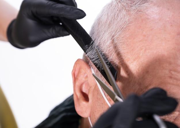 Gros plan, image, de, homme aîné, dans, salon barbier., coiffeur, coupe cheveux, à, ciseaux