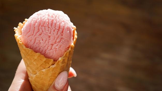 Gros plan image de main de femme tenant un cornet de gaufres fraîches avec de la crème glacée à la framboise sur le fond en bois