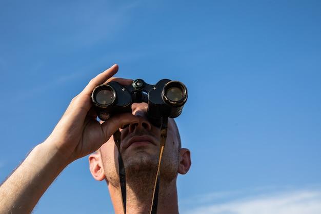 Gros plan sur l'image de la main d'un homme chauve tenant ou regardant, regardant à l'aide de jumelles sur un ciel bleu nuageux.
