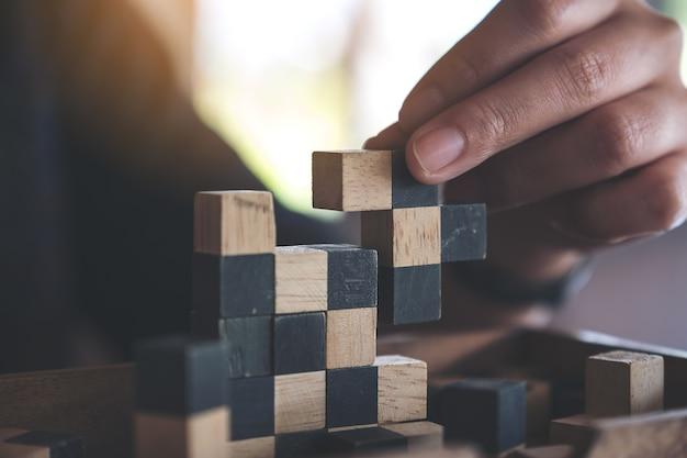 Gros plan image de personnes jouant et construisant jeu de puzzle en bois