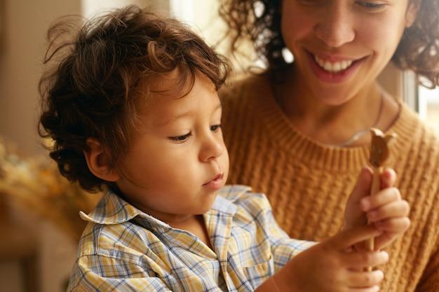 Gros plan image de petit garçon curieux aux cheveux bouclés et visage potelé jouant avec un jouet en bois assis sur les genoux de la mère. photo recadrée de jeune femme hispanique souriant largement, prenant soin de son fils mignon