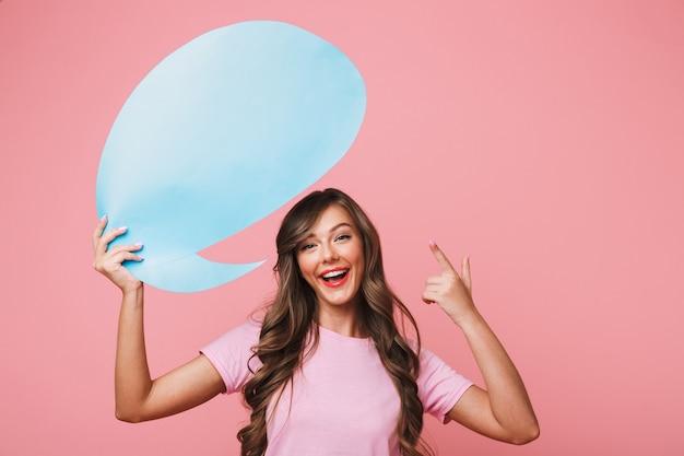 Gros plan de l'image de la publicité girl 20s tenant et pointant le doigt sur une pancarte vide au-dessus de sa tête, copyspace pour votre texte, isolé sur fond rose