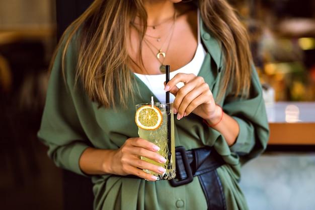 Gros plan image recadrée de femme tenant une limonade cocktail savoureuse sucrée, tenue tendance hipster élégante et bijoux élégants, couleurs toniques, atmosphère de bar.