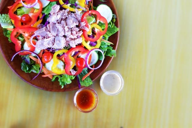 Gros plan image de salade mixte de thon coloré servir sur une plaque en bois